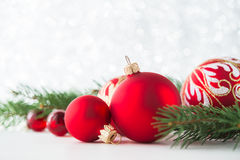 Red ornaments and xmas tree on glitter holiday background. Merry christmas card. Stock Image