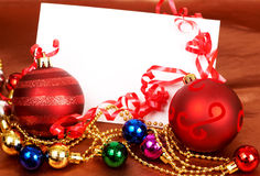 Red and other colorful Christmas baubles. And white card with copy space Royalty Free Stock Photography