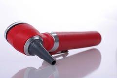 Red otoscope lying on white background Royalty Free Stock Photography
