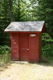 Red Outhouse. In the woods Stock Photo