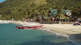 Red outrigger boat on clean white sand beach with a beautiful house, Philippines stock video