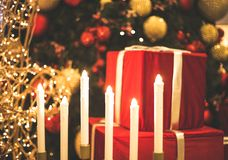 Candles and gifts for new year. Red package new year gifts near the tree with lights stock image
