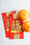 Red packets and mandarin oranges, golden Chinese letter means lu Royalty Free Stock Photo