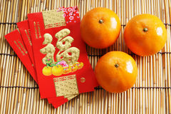 Red packets and mandarin oranges, golden Chinese letter means lu Stock Photography
