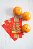 Red packets and mandarin oranges, golden Chinese letter means lu Stock Photo