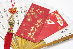 Red Packets and Trinket on Paper Fan. Closeup of Red Packet and Trinket on Chinese Fan Royalty Free Stock Photos