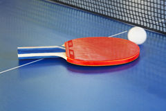 Red paddle, tennis ball on blue ping pong table Royalty Free Stock Photos