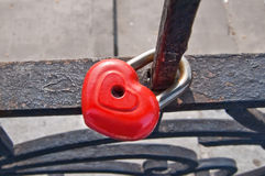 Red padlock. In the form of heart close to the fence in the background of concrete pavement Royalty Free Stock Photography