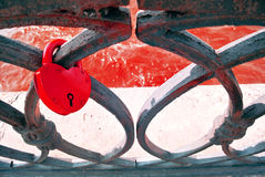 Red padlock on a black lace abstract metallic heart Royalty Free Stock Images