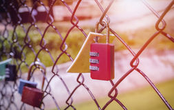 Red padlock hanging on metal fence. Old and rusty red padlock hanging on metal fence Stock Photo
