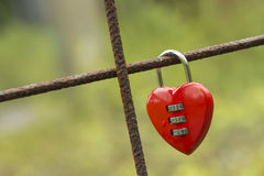 Red padlock in heart shape. Red padlock in the shape of a heart fixed to a rusted concrete wire construction Royalty Free Stock Photos