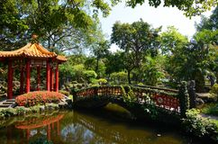 Red pagoda reflecting in a small pond at Jieshou Park across from the Presidental Office in Taip. Taipei, Taiwan - August 5, 2017 - A red pagoda and small bridge Royalty Free Stock Images