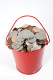 Red Pail Filled with Coins Stock Photo