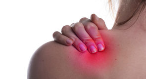 Red Pain. A woman hold her shoulder in pain. The area on the shoulder is higlighted to symbolize the pain stock image