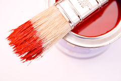 Red Paint. A bucket of red paint with a paint brush resting on top stock image
