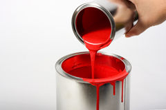 Red Paint. A hand pouring red paint from a small container to a larger one royalty free stock image