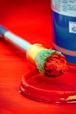 Red paint on brush with tin Royalty Free Stock Image