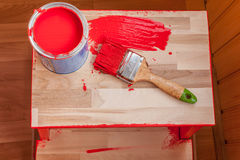 Red paint and brush on wood chair. Workplace royalty free stock photos