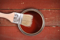 Red paint can with brush. On wooden plank background royalty free stock photos