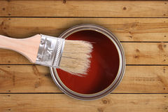Red paint can with brush on wooden floor Royalty Free Stock Photography