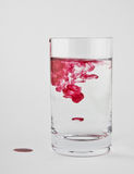 Red paint is dissolved in a glass Stock Photography