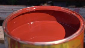 Red paint in a jar, close-up. Open bank with red paint stock footage