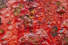 Red paint over a metallic textured and rusty background. Royalty Free Stock Photography