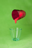 Red paint pouring to a blue glass from a flying red one Royalty Free Stock Photos