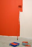 Red paint roller by wall Stock Photo