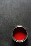 Red paint tin. Tin of vibrant red paint on slate background stock images