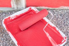 Red paint in tray with roller by old barn. Red paint tray roller old barn bright royalty free stock photo