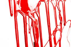 Red paint on a white background. Red paint drips on a white background. Paint flows royalty free stock images