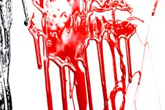 Red paint on a white background. Red paint drips on a white background. Paint flows stock images