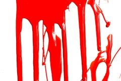 Red paint on a white background. Thick red paint on a white background. Paint flows stock photography