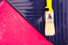 Red paint with yellow brush in tray. Top view. Royalty Free Stock Photos