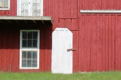 Red painted barn with white door and window trim Stock Photos