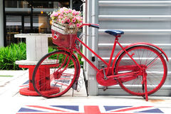 Red painted bicycle with a bucket of flowers Stock Photography