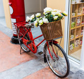 Red painted bicycle with a bucket of white flowers Stock Photo