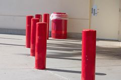 Red painted concrete poles and matching garbage can near a building royalty free stock image