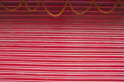 Red painted corrugated metal door and flowers garland Stock Photography