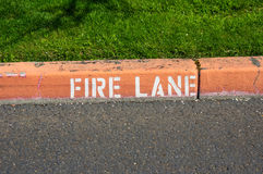 Red painted curb with fire lane sign Royalty Free Stock Photography