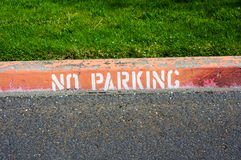 Red painted curb with a no parking sign Royalty Free Stock Photography