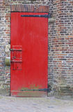Red painted door with heavy security bolts and brick wall Stock Photo
