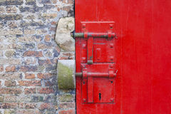 Red painted door with locks and brickwork Royalty Free Stock Images