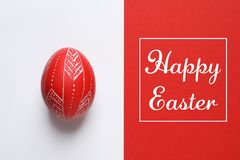Red painted egg and text Happy Easter on color background