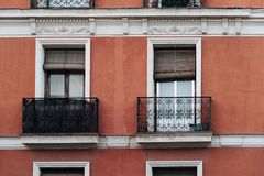 Red painted facade of classic residential building. Madrid, Spain - May 1, 2017: Red painted facade of classic residential building with iron balconies in Madrid Stock Photo