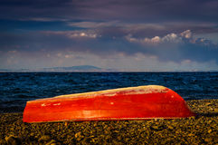 Red Painted Reverse Rowboat On Shoreline Stock Image