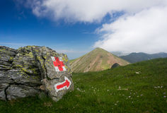 Red painted sign and arrow in the mountains of Romania Royalty Free Stock Photo