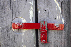 Red painted steel latch on barn door. Stock Images