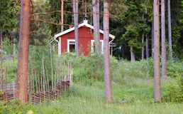 Red painted swedish summer house. In the forest stock image